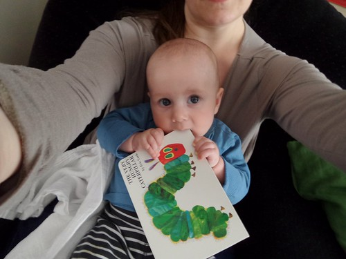 baby sitting on mother's lap, chewing a cardboard book