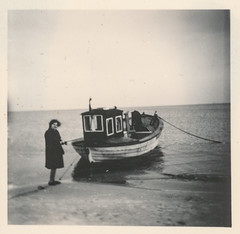 Woman stands next to a small boat