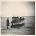 Small photo of Woman stands next to a small boat