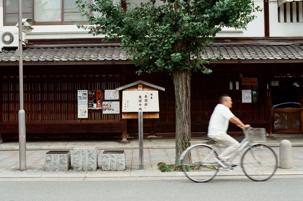 寺町通 京都 Kyoto / Kodak ColorPlus / Nikon FM2 2015/09/27 整理照片的時候發現我那時候在寺町通也拍了滿多街上騎腳踏車的路人,這裡街道不寬,兩旁都有看起來好像是歷史很久的店家,店家門面都很有特色。  我想起來了,那時候拍照有規定自己畫面中一定要有當地人入鏡,因為之前拍太多空無一人的畫面,畫面太過空寂。  Nikon FM2 Nikon AI Nikkor 50mm f/1.4S Kodak ColorPlus ISO200 0985-0034 Photo by Toomore