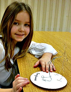Child with wire sculpture creation