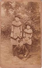 Outdoor portrait of three children in a garden by J. A. Harrison (c.1880)