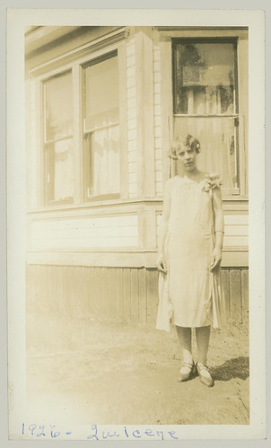 Woman standing at the corner of a house