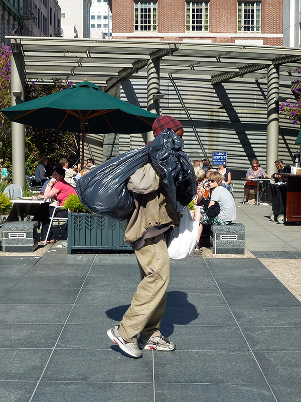 A homeless person walking along Market Street with plastic rubbish bags with his possessions