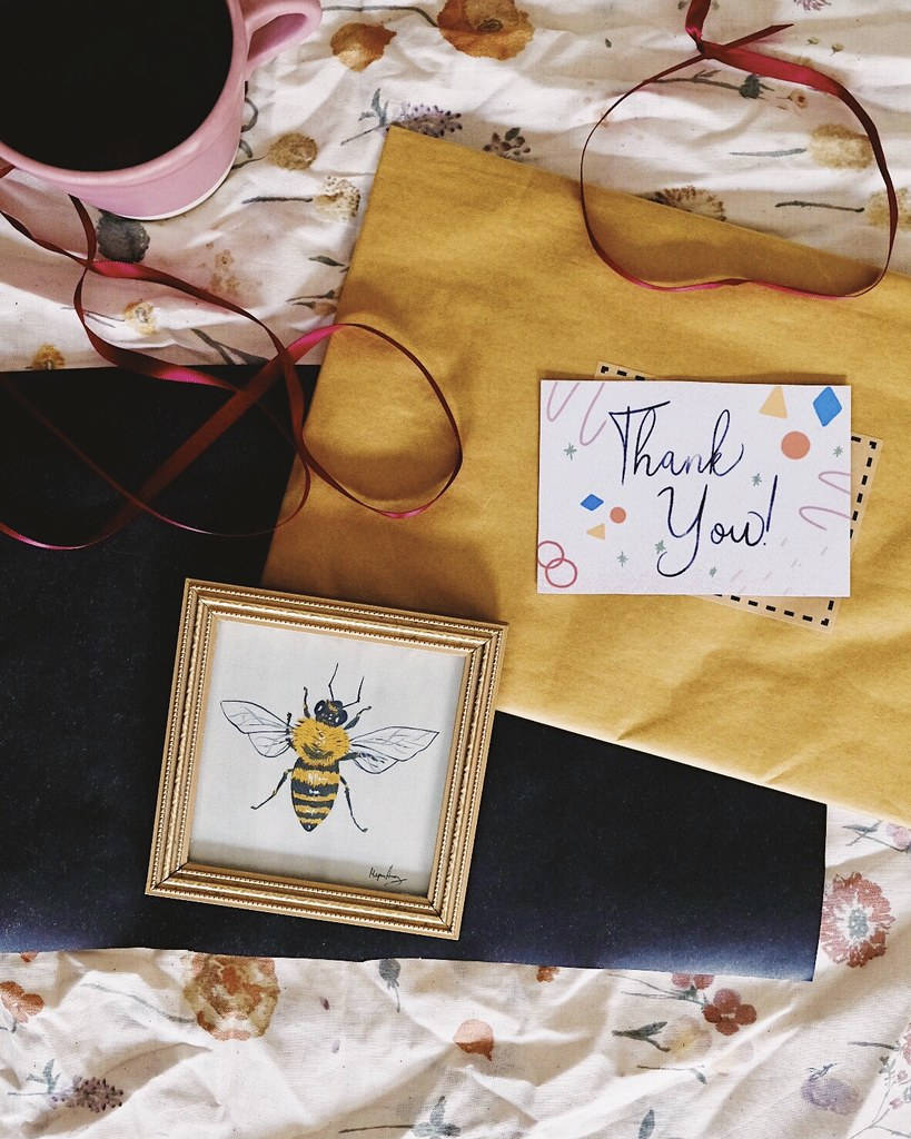 flatlay with painting of a bee surrounded by packaging and ribbon
