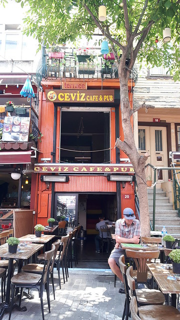 A tall, narrow building painted orange with table and chairs outside, Asian side of Istanbul, Turkey