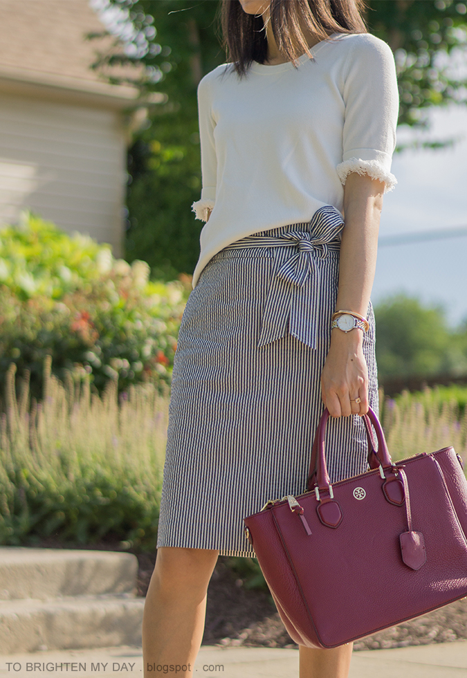 white sweater with fringe, blue striped seersucker pencil skirt with bow tie, two tone watch, rose gold cuff, morganite ring, burgundy red tote