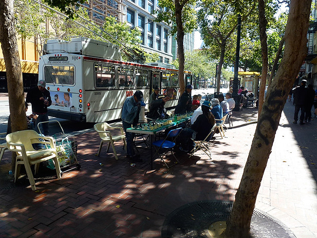 Lines of tables occur along Market street san francisco where mainly homeless people play chess