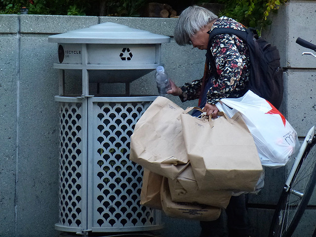 A Lady sorting through local San Francisco street for recyclable bottles that she can obtain some money from