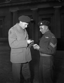 Lieut.-Col. J.F.R. Akehurst, Commanding Officer, 2nd Battalion, First Special Service Force, examines Sgt. Tommy Prince's Military Medal... / Le lieutenant-colonel J. F. R. Akehurst, commandant du 2e Bataillon de la Première Force de Service spécial,