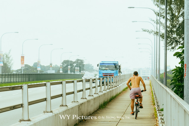 2018 Singapore. Cyclist on Nicoll HIghway on hot day.