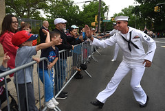A Sailor high-fives a child during the Staten Island Fleet Week Memorial Day Parade.