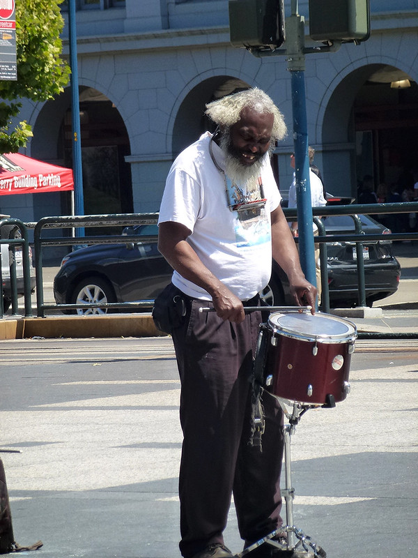 Homeless man earnestly playing a drum for money on a San Franciscan street