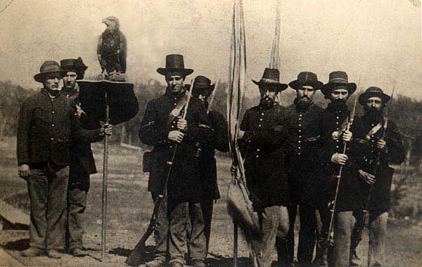 The Wisconsin 8th Volunteer Infantry Eagle Regiment with their mascot, Old Abe, at Vicksburg in July 1863. Eagle-bearer Edward Homaston is probably holding the perch. Sgt Ambrose Armitage is third from left. Original Glass Plate Negative from the J. Mack Moore Collection, The Old Court House Museum Vicksburg, Mississippi.