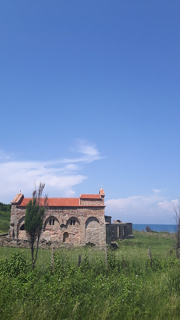 An ancient church in a green field with the ocean behind. Albania