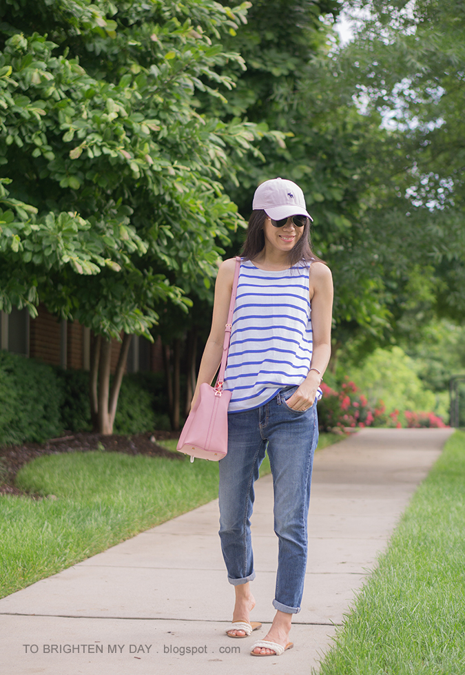pink baseball cap, striped sleeveless top with bow tie, pink bucket bag, girlfriend jeans, sandals with fringe embellishment