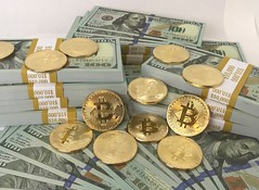 Bitcoins and Cryptocurrency coins on $10,000 straped stacks of $100 dollar bills cash money