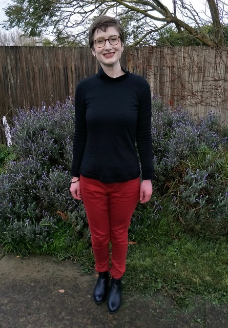 A woman stands in front of a garden fence. She wears a black skivvy, red jeans and black ankle boots. She is smiling.