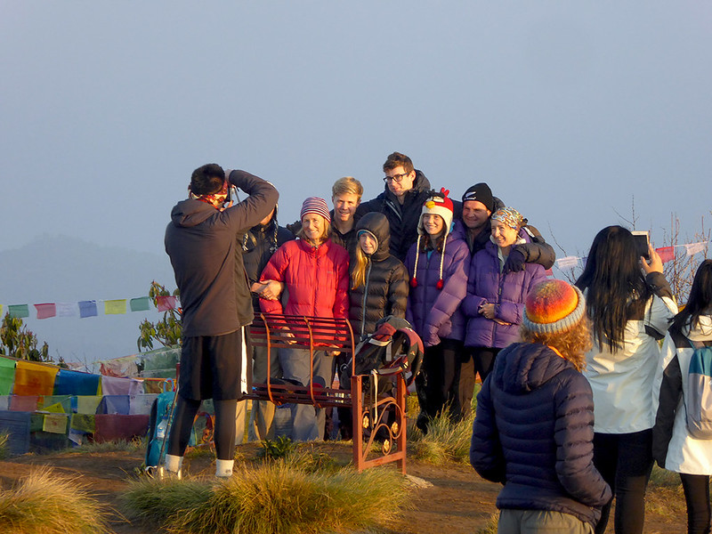 Tourist taking a group picture on top of Poon Hill after sunrise, celebrating seeing a spectacular panoramic view of the Annapurna Mountains