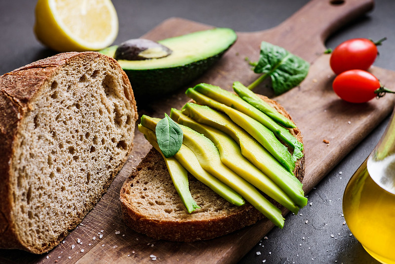 Avocado and rye bread toast on cutting board