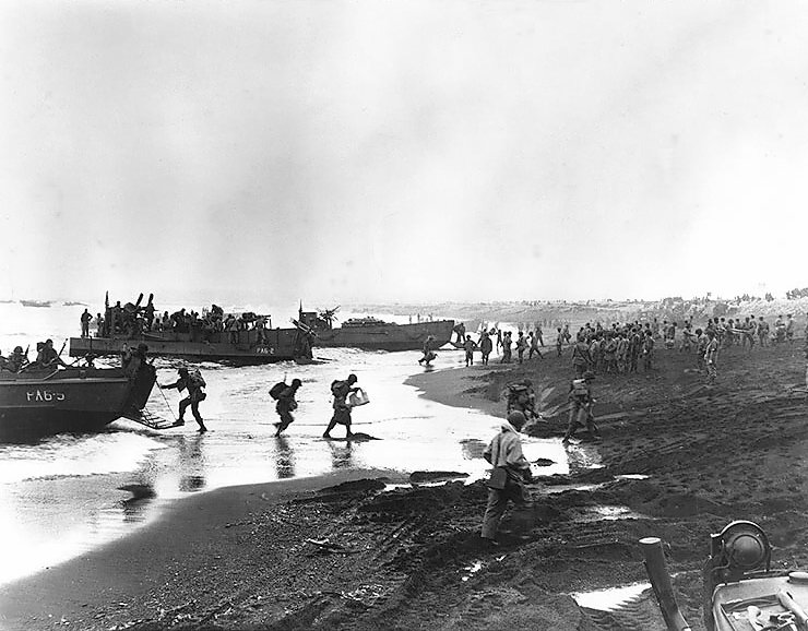 Attu Invasion, Soldiers unloading LCPR and LCM type landing craft on the beach at Massacre Bay, Attu, Alaska, on May 12, 1943. Boats are from USS Heywood (APA-6). Note the Military Policeman overseeing operations from his position near the right side of the image. Source: US Naval Historical Center Photo #: 80-G-50848