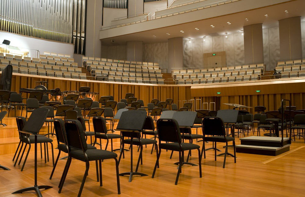 photo of concert stage with chairs and music stands