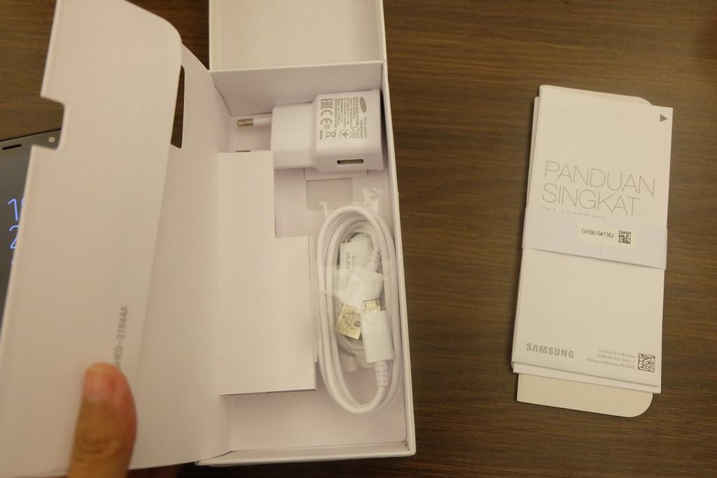 Boks Galaxy A6 Plus berisi charger, kabel USB, earphone, dan buku petunjuk penggunaan Galaxy A6 Plus (Liputan6.com/ Agustin Setyo W)