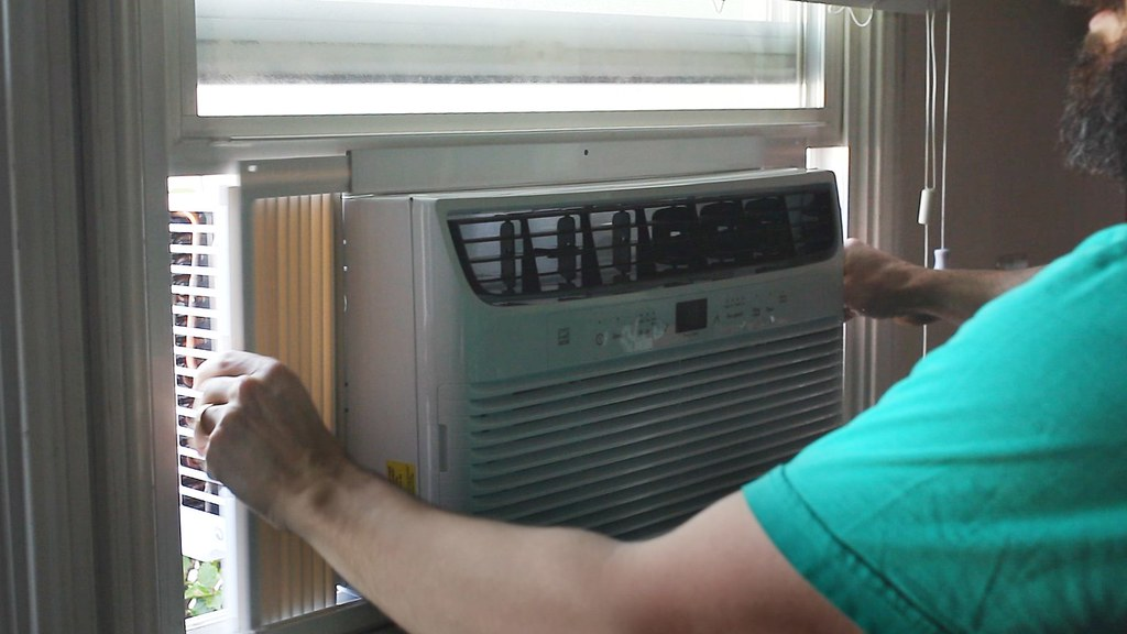 Man installing an air conditioning unit in a window