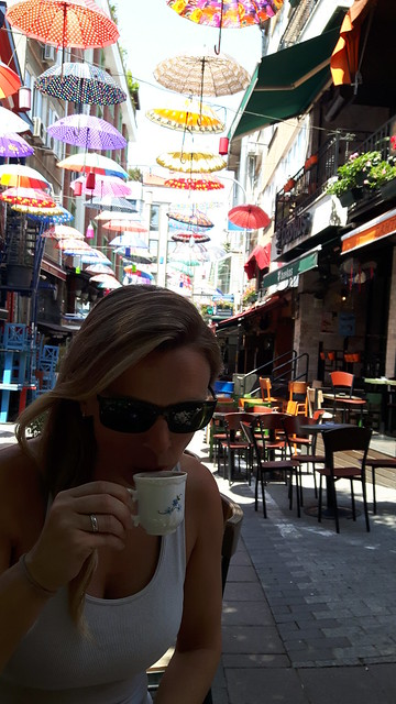 A lady drinking coffee with a street filled with umbrellas behind.