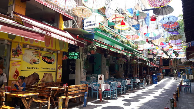 A street lined with cafes and colourful umbrellas overhead on the Asian Side of Istanbul, Turkey