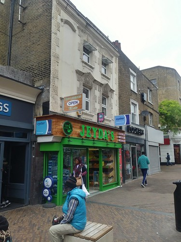 Jeyda's convenience store is notable for signage outside promoting their sale of the Oyster transit fare card, Mare Street/Narrow Way pedestrian zone, Hackney, London
