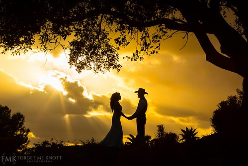 wedding bride groom couple cowboy country dusk dawn sunset sunrise clouds cloudy jamul losangeles oc orangecounty sandiego steelecanyon steelecanyongolfclub california weddingphotography silhouette sunrays godrays dramatic framing composition holdinghands cowboyhat southerncalifornia countrywedding countrytheme