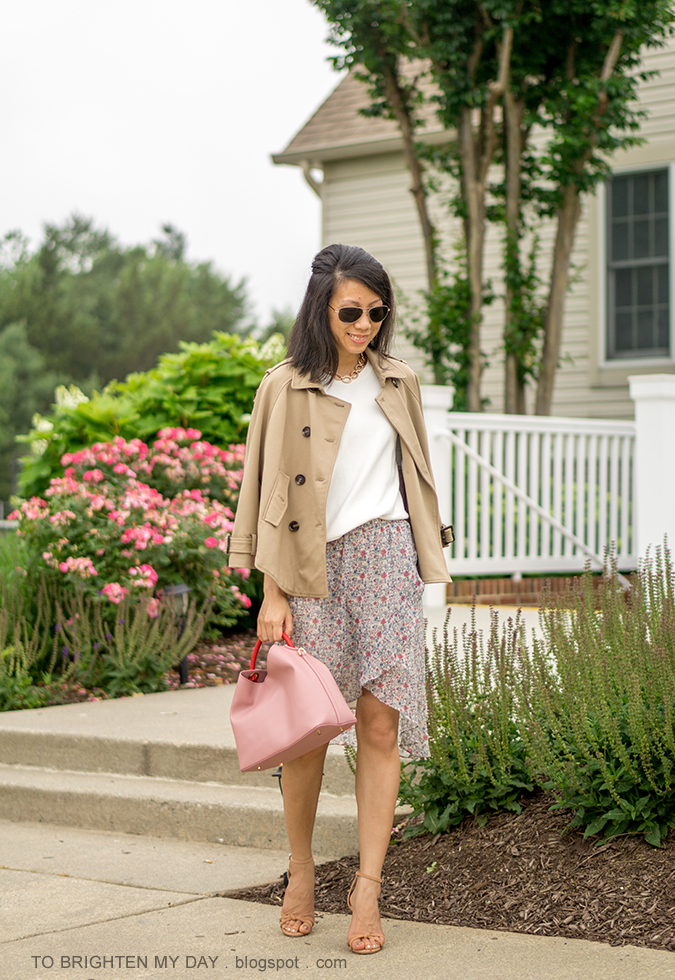 trench cape, white fringe sweater tee, gold watch, floral wrap skirt, pink tote with red handle, brown sandals with knot