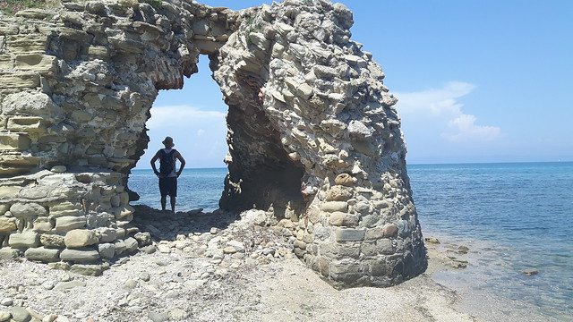 A man standing in an arch of a castle ruins in Cape of Rodon, Albania