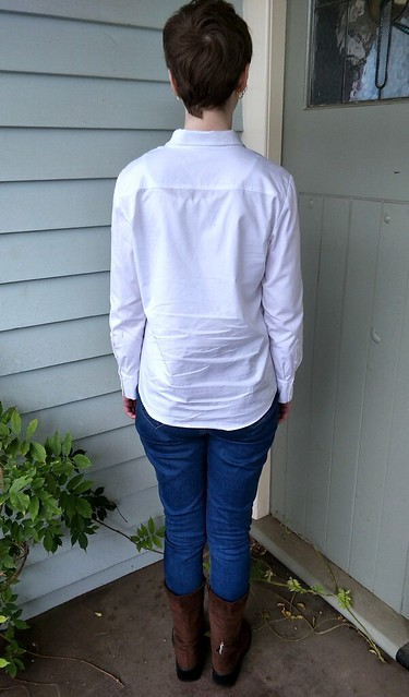 A woman stands in front of blue weatherboard facing away from camera. She wears a white button up shirt and blue jeans.