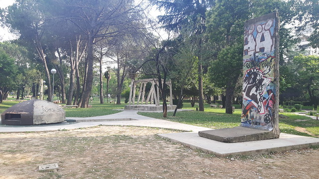 A bunker, checkpoint and piece of Berlin Wall in a park in Tirana, Albania
