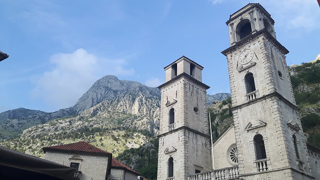 Cathedral with two square towers with mountains behind in Kotor, Montenegro.