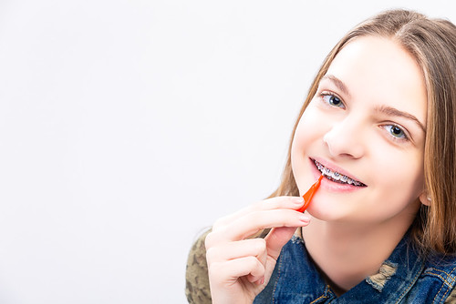 Dental Health Ideas and Concepts.Closeup Portrait of Caucasian Female Teenager With Teeth Braces. Cleaning Brackets Using Bristle Brush.