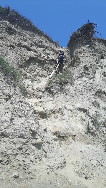 A man climbing up a cliff in Cape of Rodon, Albania