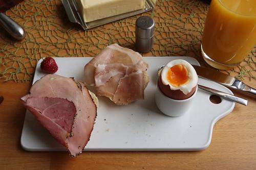 Pfefferschinkenbraten und Schinkenspeck auf frisch gebackenem Brötchen zum Frühstücksei