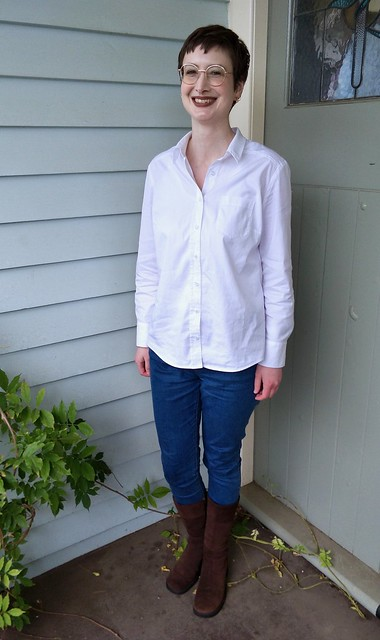 A woman stands in front of blue weatherboard. She wears a white button up shirt and blue jeans.