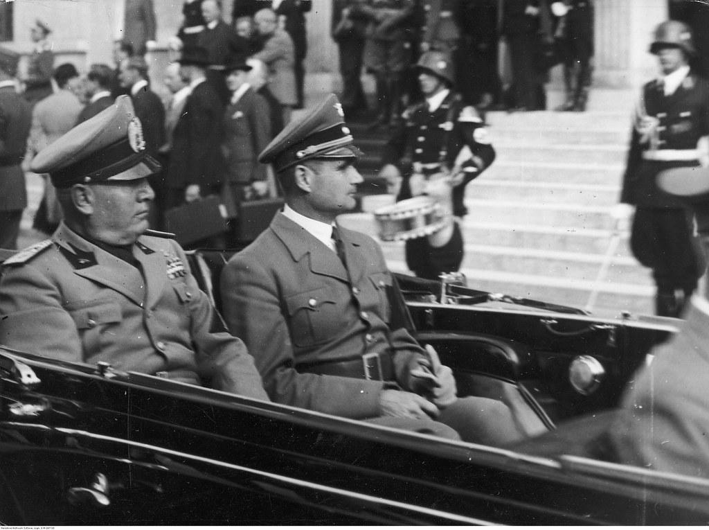 Премьер-министр Италии Бенито Муссолини (слева) и германский министр без портфеля Рудольф Гесс отъзжают на машине от Главного железнодорожного вокзала