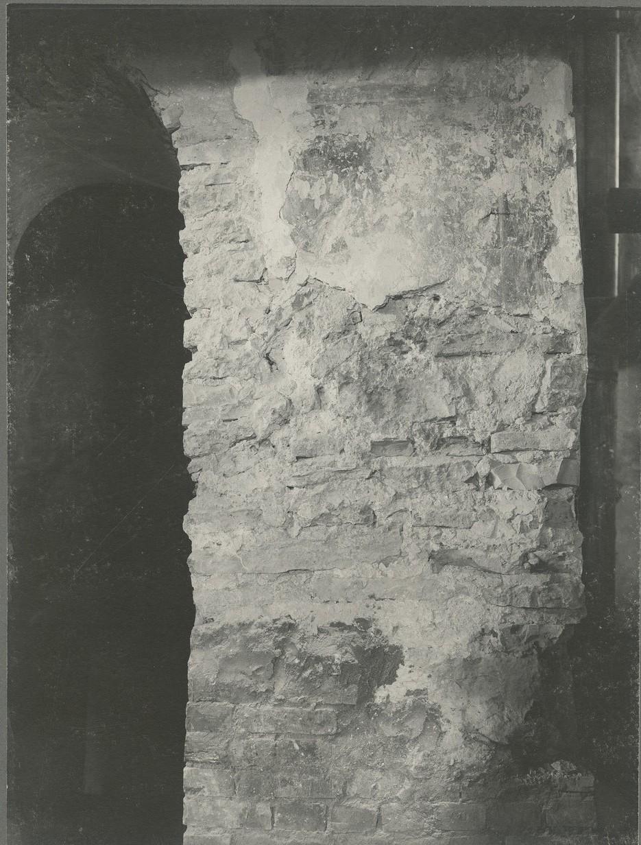 Часть оголённой до кирпичной кладки стены с фрагментами краски на небольшом куске штукатурки
