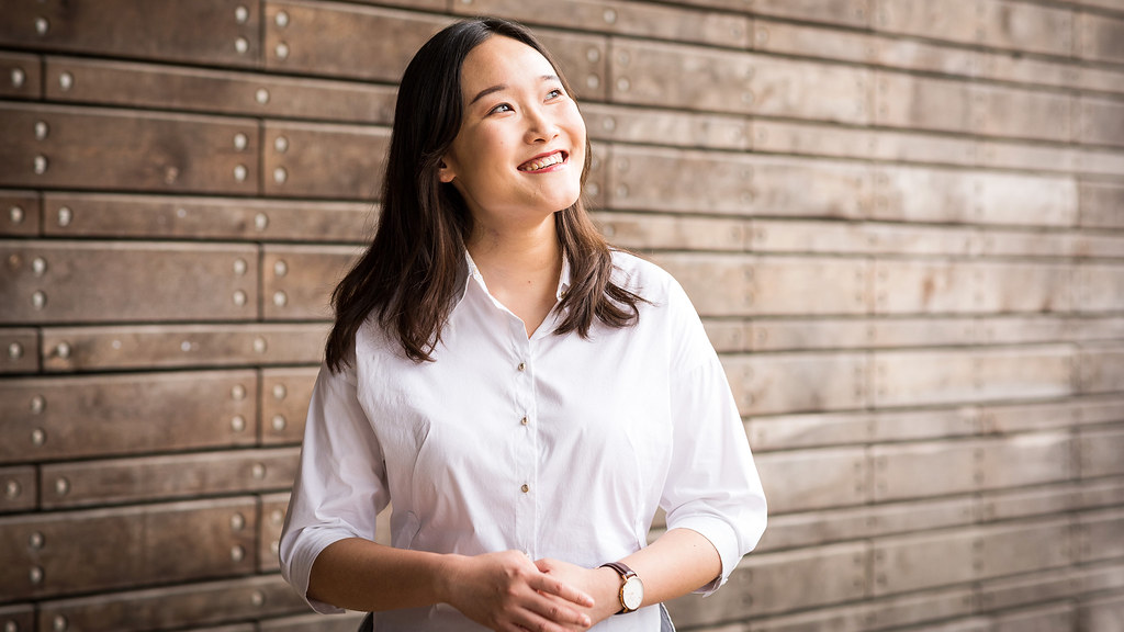 A young woman smiling and looking upwards into the middle distance in front of a wooden wall.