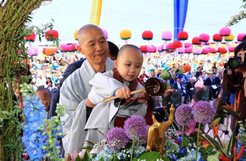 Seorang bhiksu mengangkat seorang samanera kecil dalam pemandian rupaka bayi Pangeran Siddhartha pada puja bakti Vesak 2562 EB, Selasa (22/5/2018)