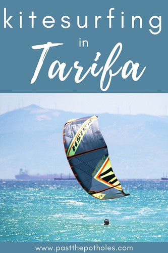 A man in the water with a kite with the text: Kitesurfing in Tarifa