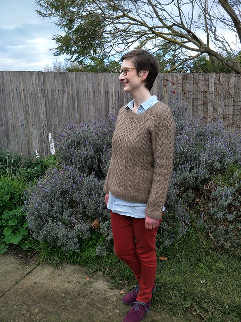 A woman stands in front of a garden fence. She wears a handknit cabled jumper, denim shirt, red jeans and purple suede boots. She is smiling.