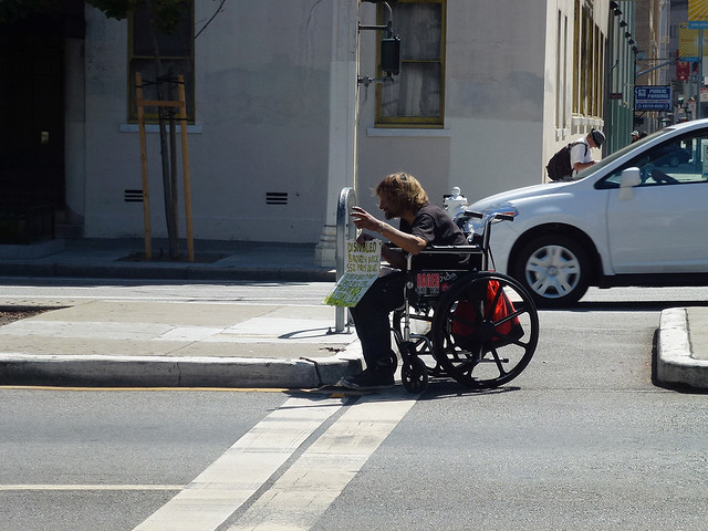 An ex US army VET in a wheelchair attempting to get the attention of passing cars in San Francisco