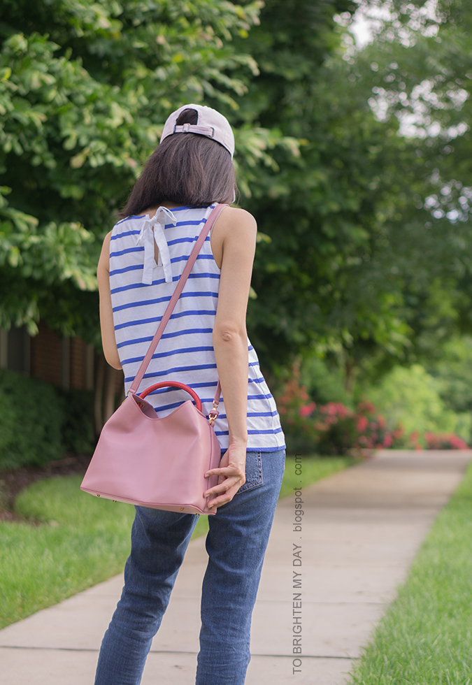 pink baseball cap, striped sleeveless top with bow tie, pink bucket bag, girlfriend jeans
