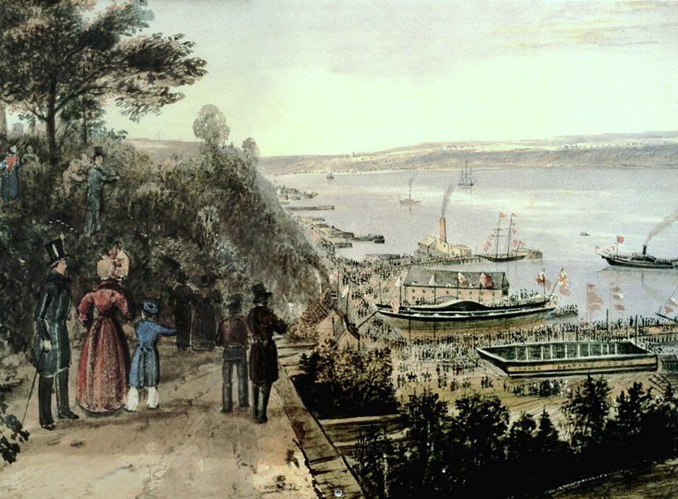 The launch of SS Royal William on April 27, 1831, at the shipyard of George Black and John Saxton Campbell, Cape Blanc, Quebec City. On the watercolor by James Pattison Cockburn, the Royal William is north of the Canada Floating Dock Dry Dock, appearing without her masts but with two wheels with side blades visible.
